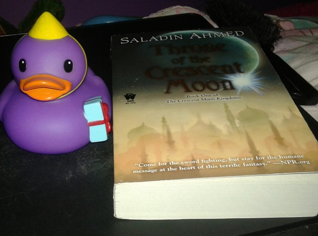 "Birthday duck Delilah with the copy of Saladin Ahmed's ""Throne of the Crescent Moon"" that Vonn got ne"