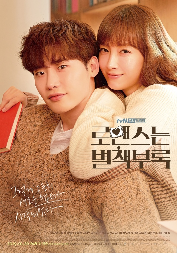 a tvN poster for Romance is a Bonus Book that shows Kang Dan-i and Cha Eun-ho cuddled up close and looking at the viewer. Dan-I has a book in her hand and a visible smile on her face. Eun-ho has a slight smile on his face